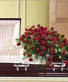Casket spray of 60 roses, plumosus, leatherleaf and myrtle accented with ribbon.
