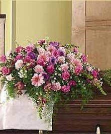 Casket spray in shades of pink, lavender and salmon.