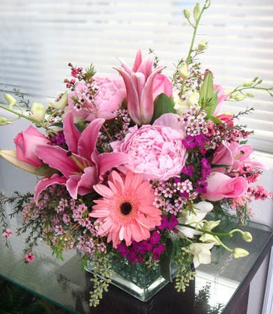 Peonies, roses, daisies, lilies, orchids, waxflower and more in a clear glass cube vase.