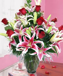 Roses and stargazer lilies in a clear glass vase.