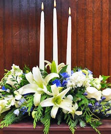 Hanukkah centerpiece with blue and white flowers, greenery, and three white taper candles