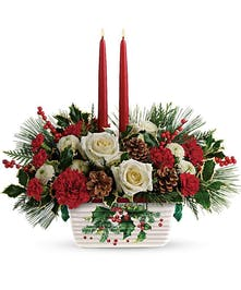Christmas centerpiece of red and white flowers, winter greenery and taper candles in Teleflora's signature dish