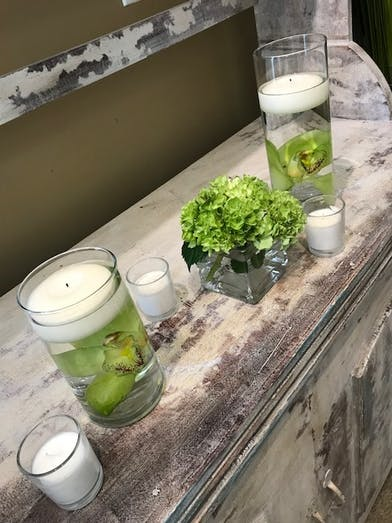 Celery green orchids and hydrangea accented with candles in a trio of vases.