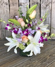 Cubed glass vase filled with orchids, roses, lilies and more.