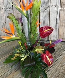 Dendrobium orchids, anthuriums and other tropical flowers in a charming container.