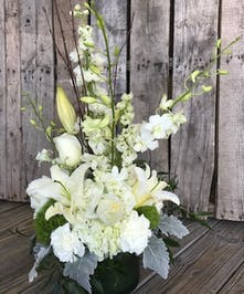 White hydrangea in a clear glass cylinder vase.