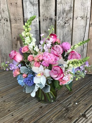 Glass vase of flowers in shades of purple white and blue