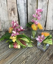 A trio of vases holding pinchsion proteas, cymbidium orchids, greenery and other tropical flowers.
