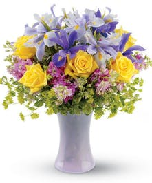 A tall lavender glass vase filled with blue iris and yellow roses.
