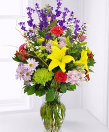 Purple larkspur, pink carnations, yellow daisies and more in a clear glass vase.