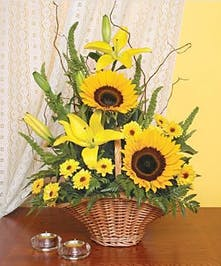 One-sided basket design of sunflowers, lilies and seasonal flowers.