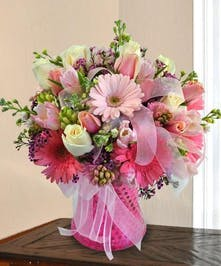 Pink roses, gerbera daisies, tulips and more in a vase with gossamer ribbon.