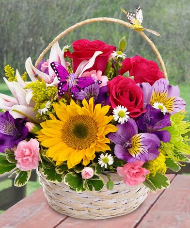 A basket filled with bright flowers with a butterfly decoration.