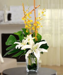 Lilies and orchids in a rectangular glass vase.