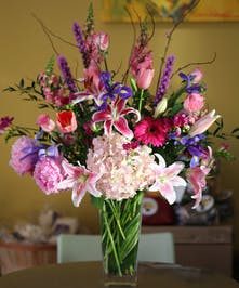 Grand bouquet of spring flowers in a tall glass vase.