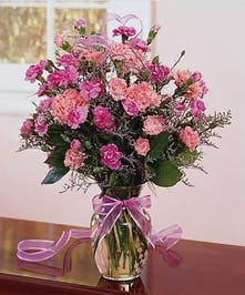 Sweet, pink carnations designed in a clear vase