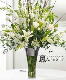 All-white luxury flower arrangement in a tall glass vase.
