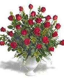 Two dozen red roses in a white sympathy urn with accent flowers.
