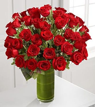 Four dozen red roses with greenery in a glass vase.