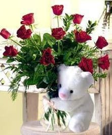 One dozen red roses in a clear glass vase held by a teddy bear.