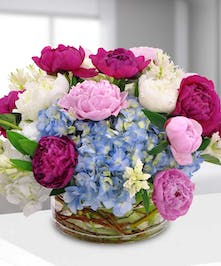 Hydrangea, hyacinths and peonies in a clear glass vase.
