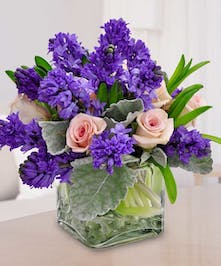 Purple hyacinths and pink roses in a glass cube vase.
