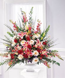 Sympathy urn arrangement of red roses, pink stargazer lilies, pink snapdragons and more.