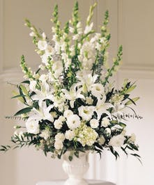 White urn of all-white flowers including lilies, gladiolus and lisianthus.