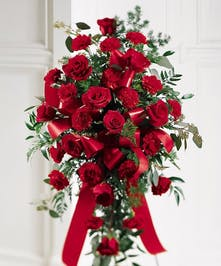 Sympathy spray of red roses and carnations accented with ribbon and presented on an easel.
