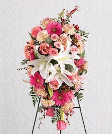 Sympathy spray with white lilies, pink roses, gerbera daisies, carnations and more.