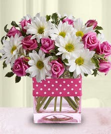 Pink roses and white daisies in a clear glass cube vase tied with a pink polka-dot ribbon.
