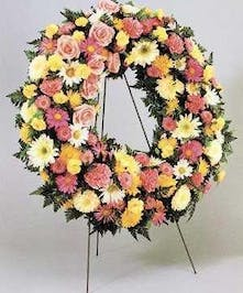 Sympathy wreath of carnations, poms, roses, daisies and assorted greenery.