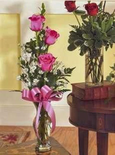 Three roses and greenery in a clear glass bud vase.