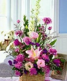 Assorted spring cut flowers in shades of lavender in a natural handled basket.