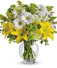 Yellow, green and white flowers in a glass vase.