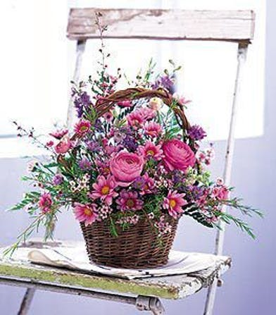 Spring basket of mostly shades of lavender & pink spring mixed flowers.