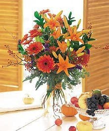 Chrysanthemums, gerberas, lilies and eucalyptus in a clear glass vase tied with a ribbon.