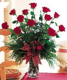 One dozen long stemmed red roses designed with winter greenery in a clear glass vase.