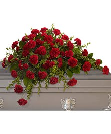 Casket spray of red carnations and greenery.