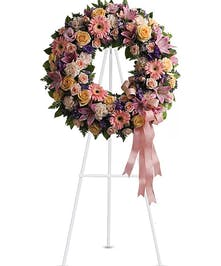 Pink sympathy wreath of roses, carnations, daisies and more.
