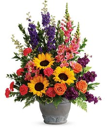 Urn filled with an array of vibrant seasonal flowers.