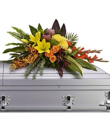 Tropical casket flowers accented with greenery.