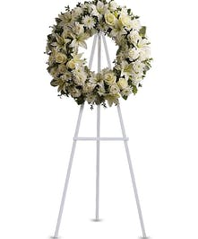 Pure white sympathy wreath of roses, ribbon and greenery.