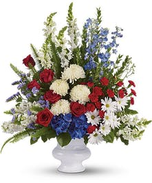 Patriotic sympathy arrangement of red, white and blue flowers.