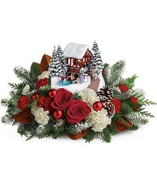 Thomas Kinkade's Snowfall Dreams keepsake surrounded by red and white flowers and winter greenery