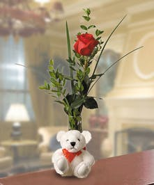 Teddy bear plush and a bud vase with a single red rose.