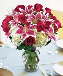 Stargazer lilies, hydrangea and roses in a clear glass vase.