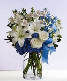 Winter bouquet of white and blue flowers accented with blue ribbon