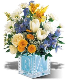 Yellow, white and blue flowers in a keepsake baby's block vase.