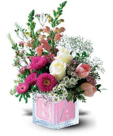 White and pink flowers in a keepsake baby's block vase.